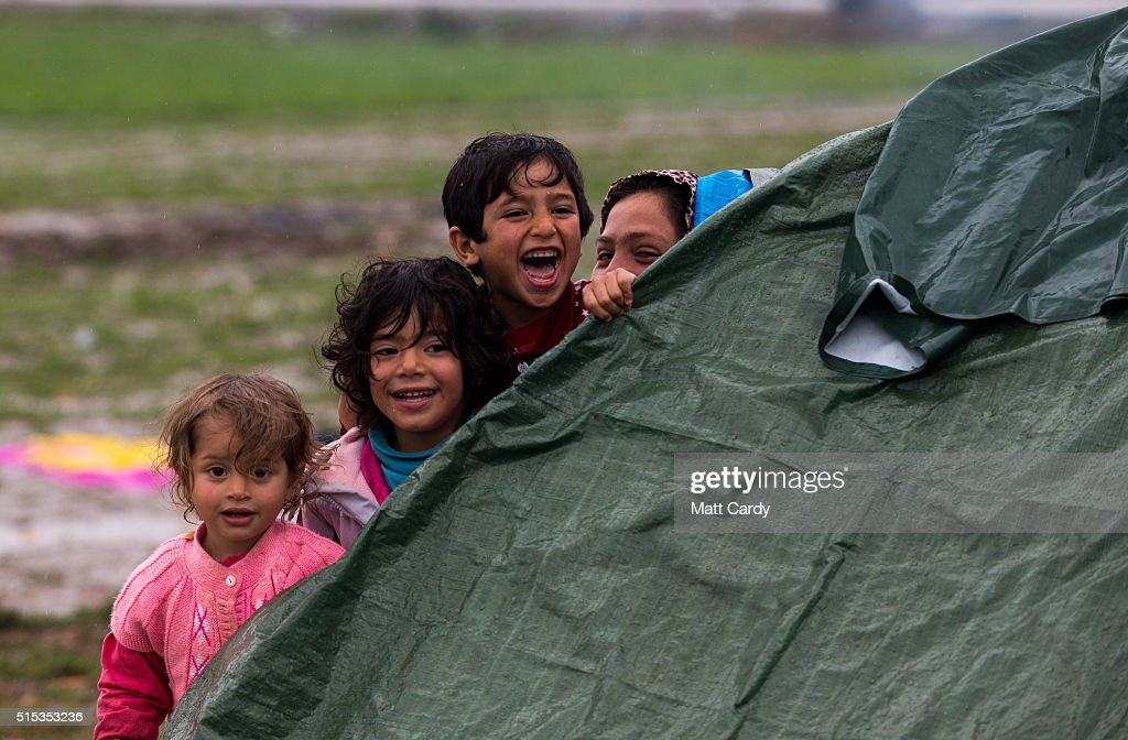 Children in a tent react as migrants stage a protest march about the continued closure of the Macedonian Greek border the Idomeni refugee camp on March 13, 2016 in Idomeni, Greece. The decision by Macedonia to close its border to migrants on Wednesday has left thousands of people stranded at the Greek transit camp. The closure, following the lead taken by neighbouring countries, has effectively sealed the so-called western Balkan route, the main migration route that has been used by hundreds of thousands of migrants to reach countries in western Europe such as Germany. Humanitarian workers have described the conditions at the camp as desperate, which has been made much worse by recent bouts of heavy rain.