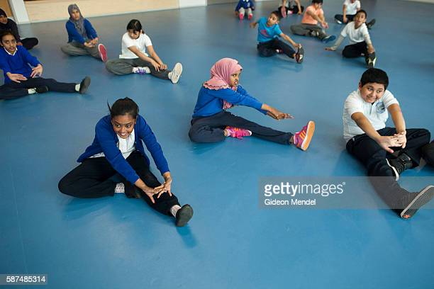 Children in a Year 6 class at Marner Primary School in Tower Hamlets stretch out as part of their warmup for a PE gymnastics lesson This is one of...