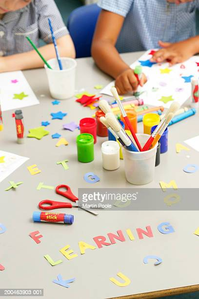 Children (5-7) in art class, 'learning' on table, elevated view
