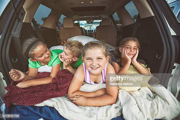 children in back of car awaiting a drive-in movie - rebecca nelson stock pictures, royalty-free photos & images