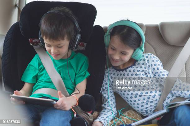 children in back seat on road trip - family inside car stock photos and pictures