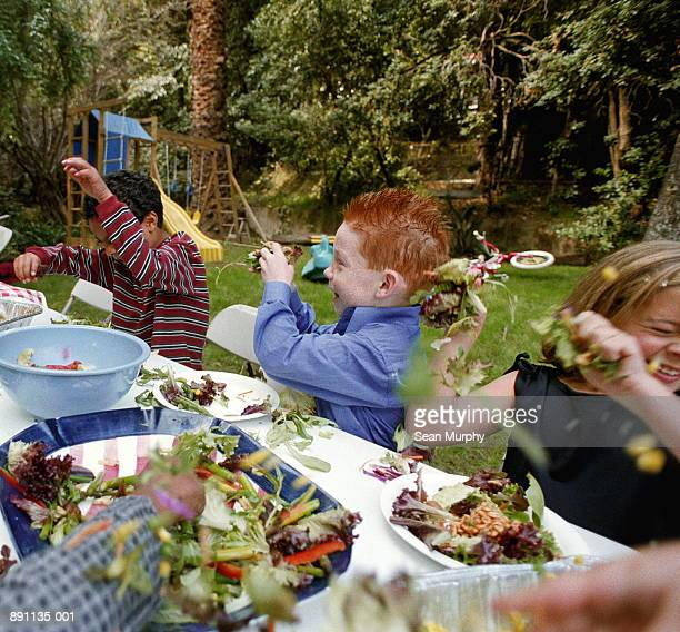 Children (5-7) in backyard throwing food at each other
