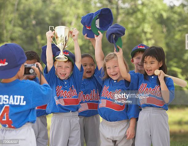 children in baseball outfits cheering with trophy - baseball team stock pictures, royalty-free photos & images