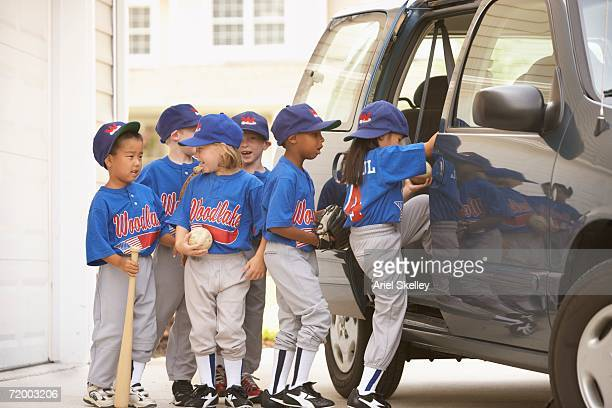 children in baseball outfits getting into car - mini van stock photos and pictures