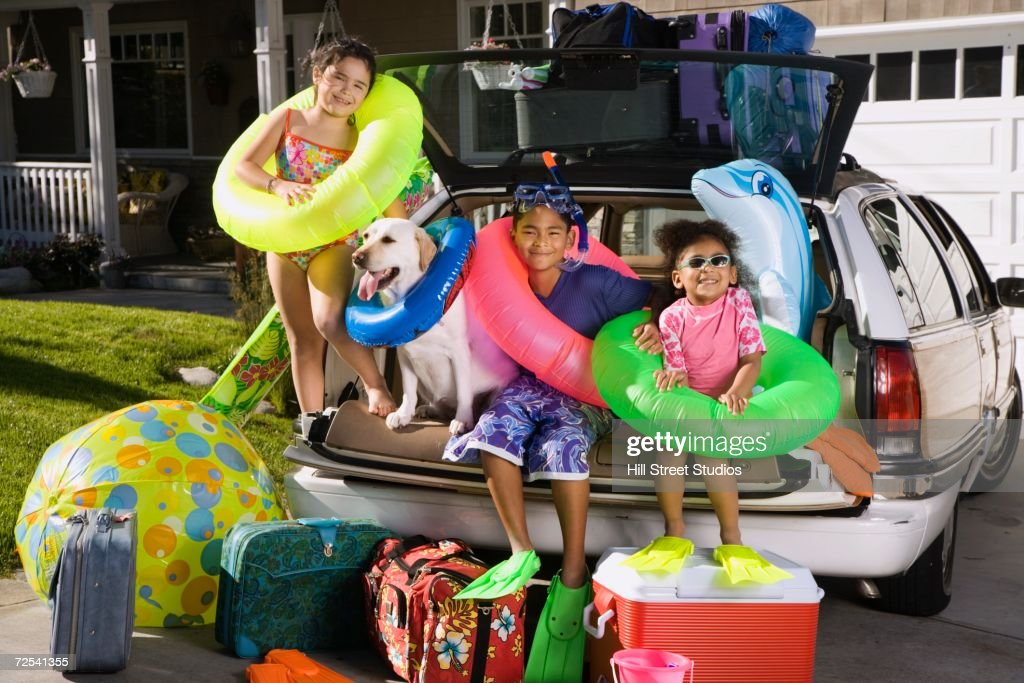 Children in beach gear sitting in back of packed car : Stock Photo