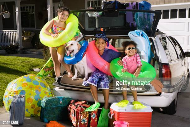 children in beach gear sitting in back of packed car - boot stock pictures, royalty-free photos & images