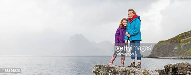 Children in bright outdoor clothing beside ocean