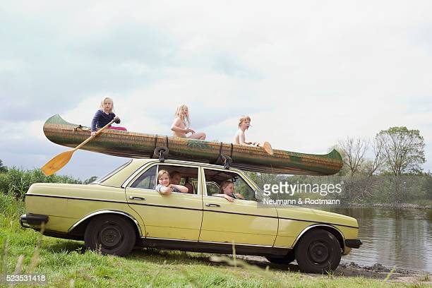 Children (5-6) in car with canoe on roof