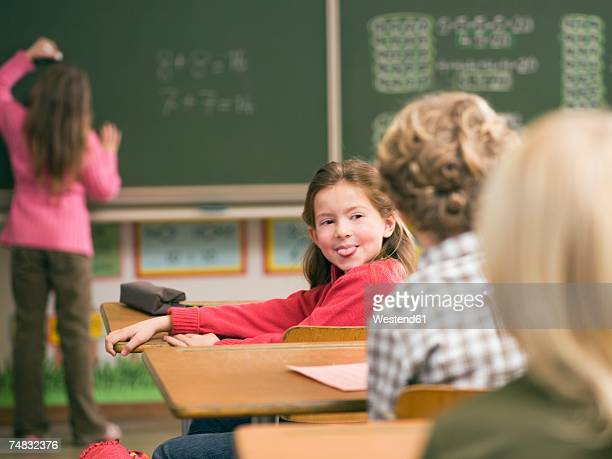 Children (4-7) in class room, focus on girl sticking out tongue