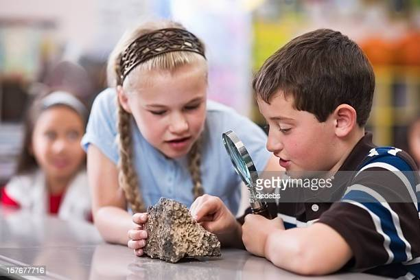 children in classroom with magnifying glass - geology stock pictures, royalty-free photos & images