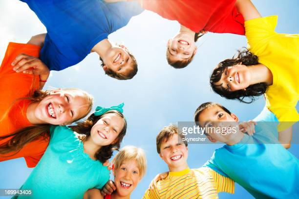 Children in colorful t-shirts against the sky.
