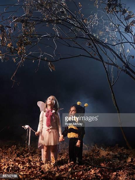 Children  in costume in dark forest scene.