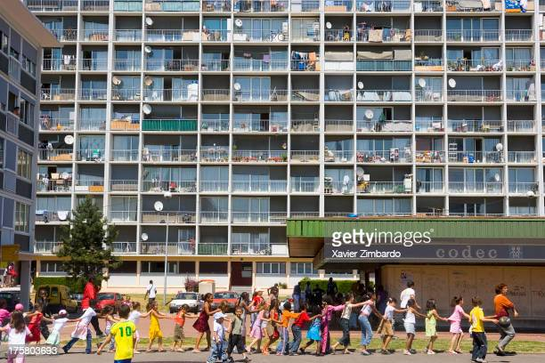 Children in council housing walking in train formation smiling on June 17 2006 in Sarcelles a Paris suburb France