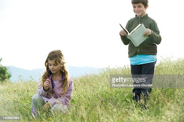 Children in field, boy reading book while girl picks wildflowers