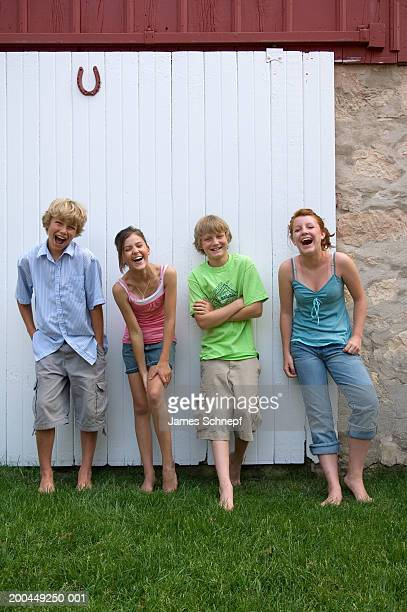 Children (10-14) in front of barn door laughing