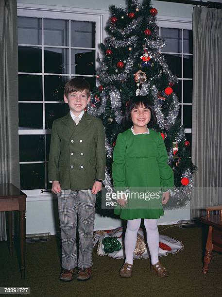 children in front of christmas tree - christmas past and christmas present stock pictures, royalty-free photos & images