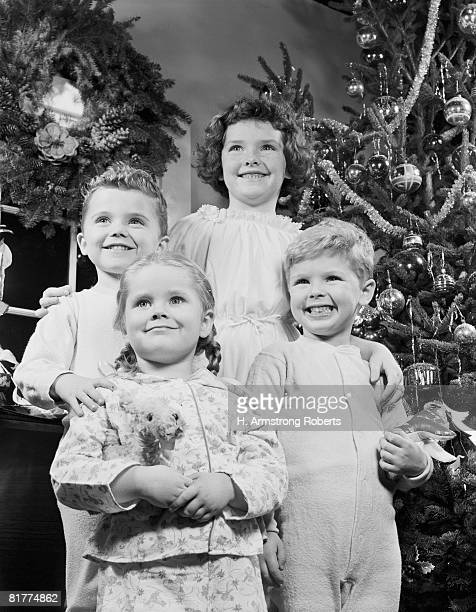 Children in front of Christmas tree.
