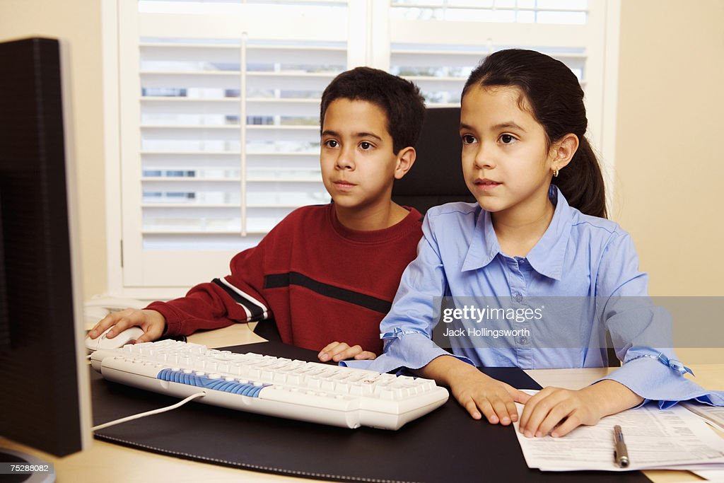 Children (8-11) in front of computer, looking at monitor : Stock Photo