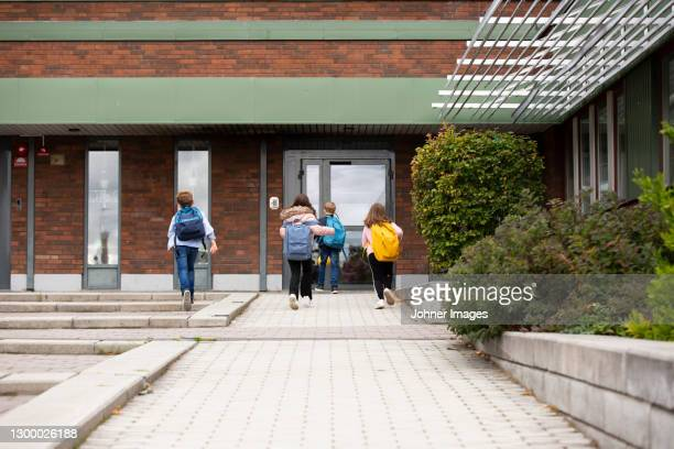 children in front of school building - entering stock pictures, royalty-free photos & images