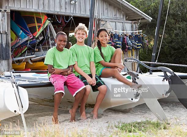 Enfants devant des équipements de sports nautiques shack