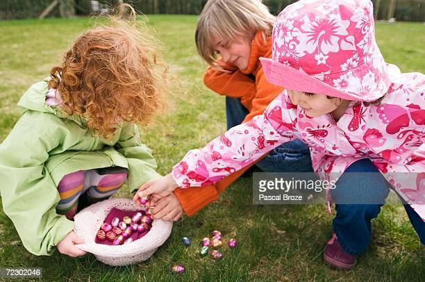 3 children in garden with Easter eggs