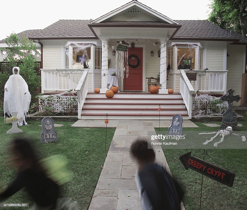 Children (4-5) in Halloween costume running at house : Foto stock