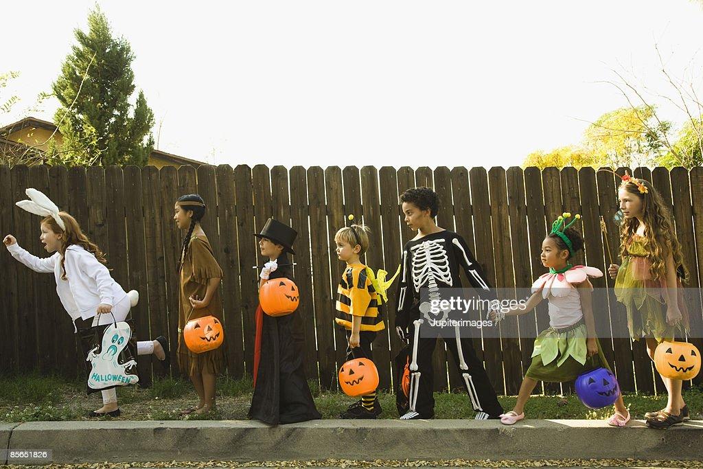Children in Halloween costumes holding hands : ストックフォト