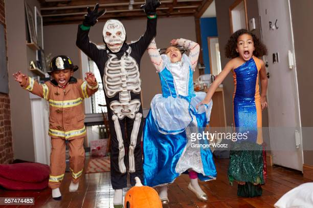 Children in Halloween costumes jumping for joy