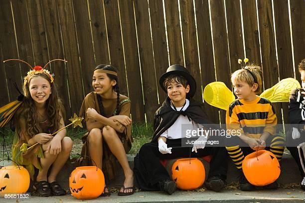Children in Halloween costumes sitting on sidewalk