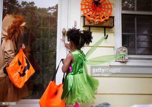 Children in Halloween costumes standing at doorway during trick or treating