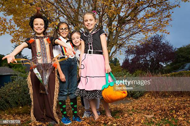 children in halloween costumes under autumn tree - poodle skirt stock photos and pictures