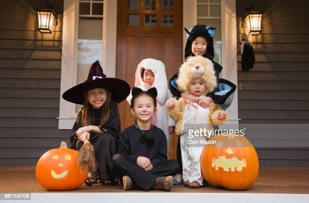 Children in Halloween costumes with pumpkins