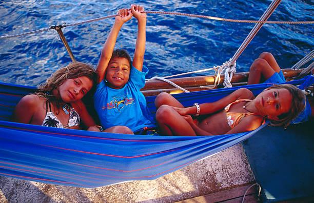 Children in hammock on yacht on Caribbean  Sea off St Barts.