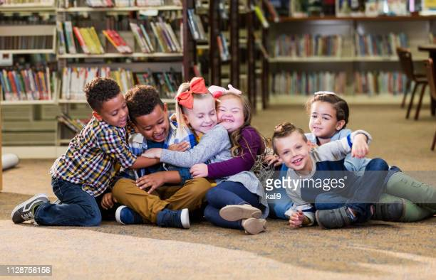 children in library, girl with down syndrome, group hug - down syndrome stock pictures, royalty-free photos & images