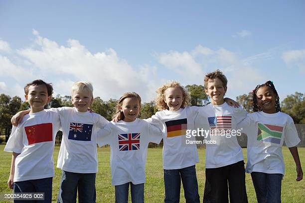 children (6-7 years) in national flag t-shirts standing arm in arm - 6 7 years stock pictures, royalty-free photos & images