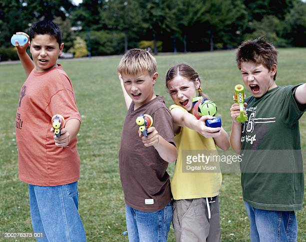 Children (9-12) in park aiming water pistols and water bombs, portrait