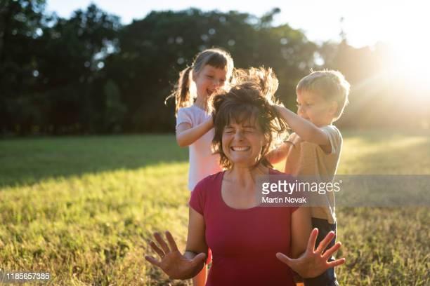 children in park messing up their mom's hair - mom flirting 個照片及圖片檔