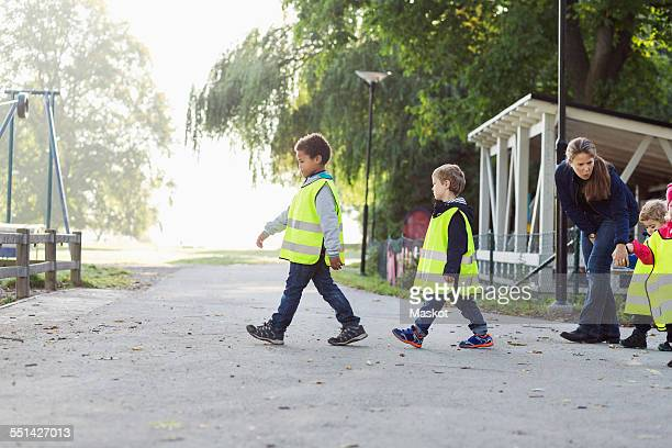 children in protective jacket with teacher walking on footpath - reflective clothing stock pictures, royalty-free photos & images
