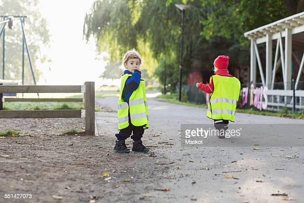 Children in protective jackets walking on footpath