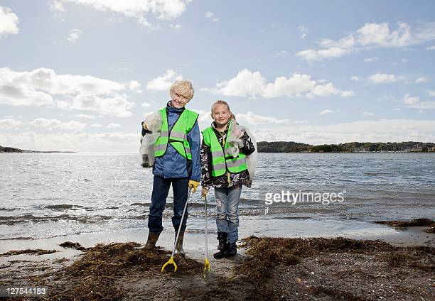 Children in safety vests cleaning beach