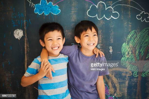 Children in school. Two boys standing with their arms around each others shoulders by a chalkboard.