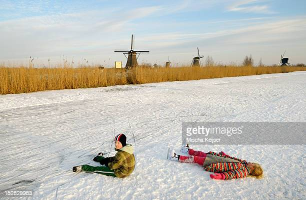 Children in skates laying on ice