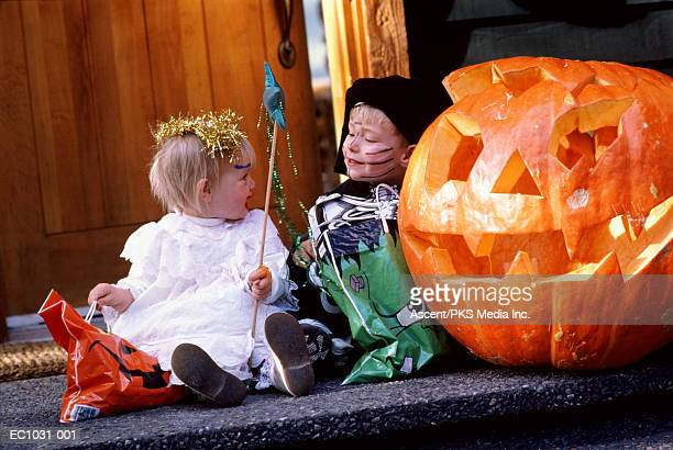 Children (2-5) in skeleton and fairy costumes waiting on doorstep