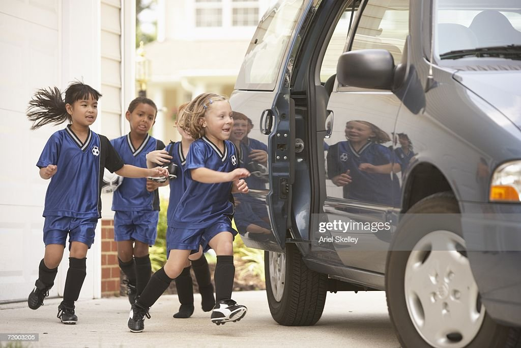 Children in soccer outfits getting into car : Stock Photo