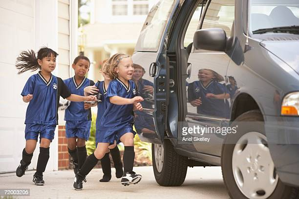 children in soccer outfits getting into car - mini van stock photos and pictures