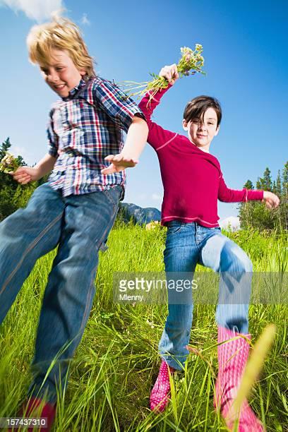 Kinder im Sommer Spaß, springen auf der grünen Wiese