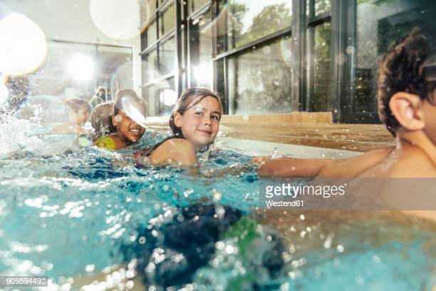 children in swimming class practicing at poolside in indoor swimming pool - schwimmen stock-fotos und bilder