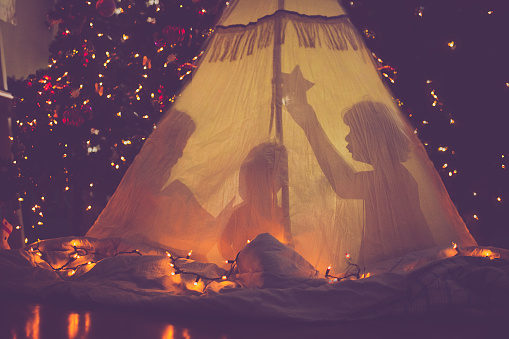 Children in tent in front of Christmas tree - gettyimageskorea