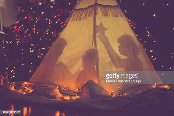 children in tent in front of christmas tree - help:contents stock pictures, royalty-free photos & images