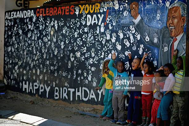 Children in the Alexandra Township stand next to a mural of Nelson Mandela on June 152013 in Johannesburg South Africa The former South African...